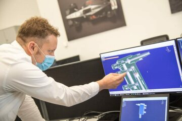 Ben Hodgkinson, Head of Mechanical Engineering at Mercedes-AMG HPP, with technical drawings of the UCL Ventura CPAP device. Photographer: Jude Palmer / Royal Academy of Engineering